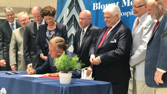 Gov. Bill Haslam is surrounded by lawmakers and law enforcement officials as he signed the TN Together law into effect Friday, June 29 outside the Blount Memorial Hospital in Maryville, Tenn.