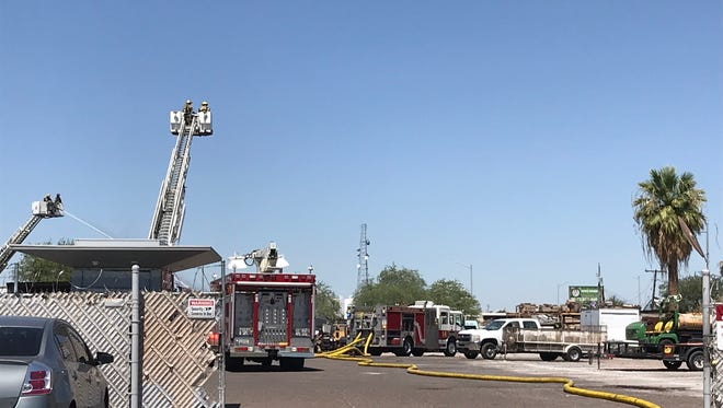Firefighters continue to put out hot spots from burning mulch and other landscaping debris at a business near 19th and Grand avenues on July 3, 2018.