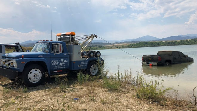 A tow truck, with the help of emergency responders, pulls out a Chevy Silverado found on Friday, July 6, 2018, in Lon Hagler Reservoir southwest of Loveland.