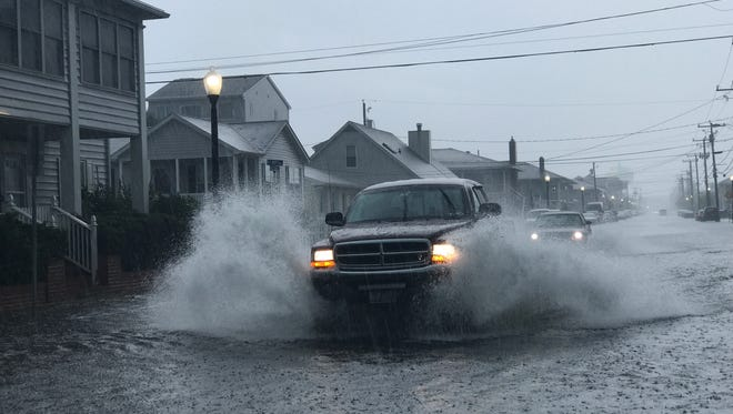 Travelers try and escape the rain on St. Louis Avenue. A storm on Friday, July 6 is flooding some spots in Ocean City.