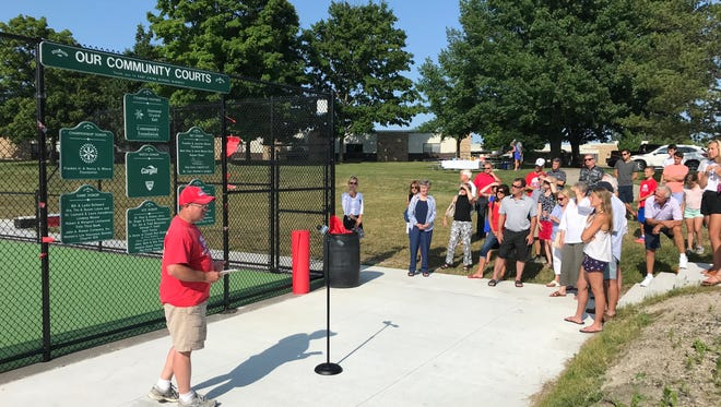 St. Clair High School tennis coach Dave Clutts speaks at a ceremony to unveil eight new tennis courts at the high school.