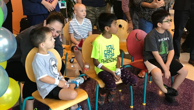 Kids welcome Geoffrey the Giraffe, who gained fame as the Toys R Us mascot, to his new home July 11, 2018, in the lobby of Bristol-Meyers Squibb Children's Hospital in New Brunswick, N.J. The 16-foot-tall fiberglass statue will be among the first things sick children and their families see as they enter.