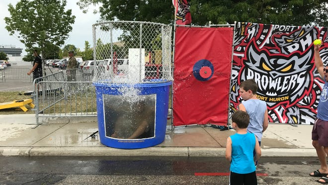 Port Huron Prowlers defenseman Joe Pace Jr. falls into the water at a dunk tank set up outside of Port Huron Yacht Club.