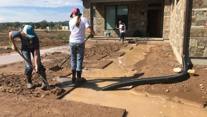 Friends and neighbors were helping homeowners clean flooded yards and basements after thunderstorms dropped more than 3 inches of rain in a single thunderstorm late July 11.