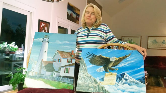 Former Department of Correction counselor Patricia May displays examples of paintings by Delaware prison inmates that decorate her home in Hockessin, Del., Monday, July 16, 2018. May, a state corrections counselor who was taken hostage during a deadly riot at Delaware's maximum-security prison, says prison officials are to blame. On Tuesday, Gov. John Carney and corrections officials will release a final report on efforts to implement 41 recommendations from an independent review team. (AP Photo/Randall Chase)