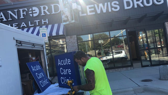 Tyler Joppa of Pride Neon prepares signs Tuesday for placement at the new building that will soon house a Lewis Drug and Sanford Acute Care Clinic, as well as PAve's rooftop patio, located  at the corner of Phillips Avenue and 10th Street in downtown Sioux Falls.