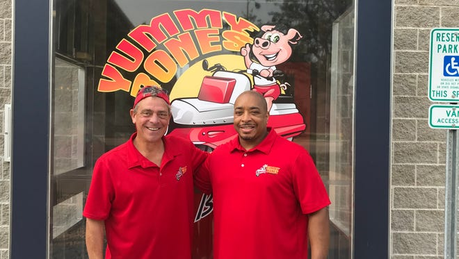 Founder and Pitmaster Robert Meredith, right, and COO Steve Smirl, left, stand outside Yummy Bones at 57 N. Macy St.