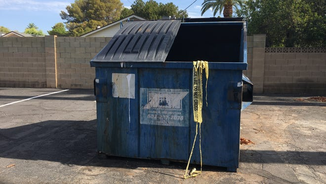 Police tape hangs from a trash bin in a parking lot at Church for the Nations in north-central Phoenix. Police officials say a man lighted himself on fire in the parking lot on July 24, 2018.