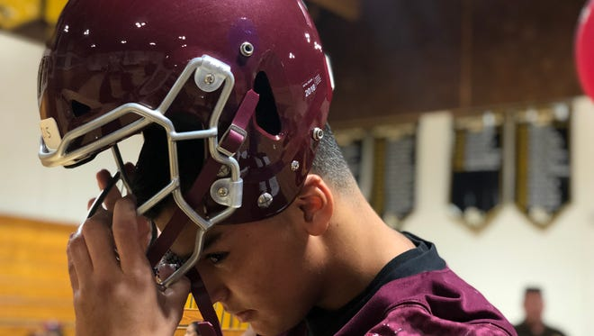 Mt. Whitney football player Anthony Valencia puts on the VICIS ZERO1 helmet on Wednesday at Golden West High School.