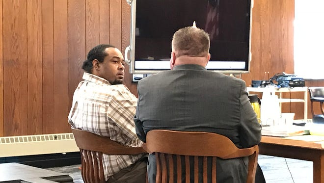 Herman Miller, left, discusses his rape and kidnapping allegations Thursday with attorney Jon Ickes during a break in his trial.