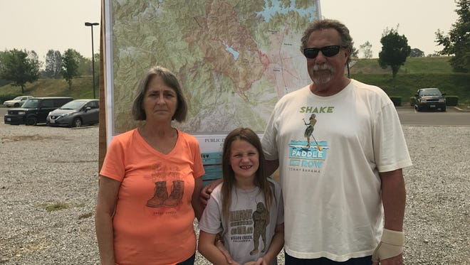 La Rue, from left, Payton and Robert Fisher stand in front of a map of the Carr Fire July 29, 2018. They evacuated and were trying to find out more about their home.