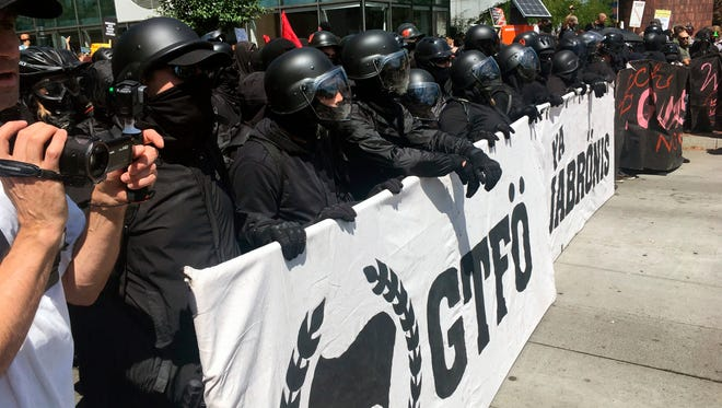 """Protesters line up Saturday, Aug. 4, 2018 in Portland, Ore. Small scuffles broke out Saturday as police in Portland, Oregon, deployed """"flash bang"""" devices and other means to disperse hundreds of right-wing and self-described anti-fascist protesters. (AP Photo/Manuel Valdes)"""