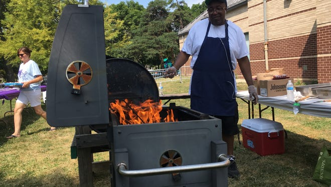 Richard Newsome cooks burgers and hot dogs at the World Peace Celebration Saturday at Sherman Park in Milwaukee.