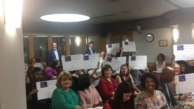 Supporters of a property tax increase to fund children's services brandish signs Monday urging Hamilton County commissioners to pass the tax.