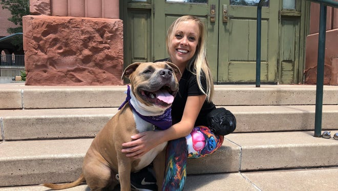 """Kristin Allen poses with her dog Mo in front of the Flagstaff City Hall building on Saturday, Aug. 4. Mo the """"screaming"""" dog was found wandering the streets of Phoenix alone. Now, more than 50,000 people follow him on Instagram."""