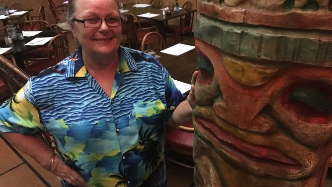 Omni Hut owner Polly Walls-Balakhani stands in front of a hand-carved tiki in the dining room of the restaurant her father, the late Maj. James Walls, opened in the 1950s.