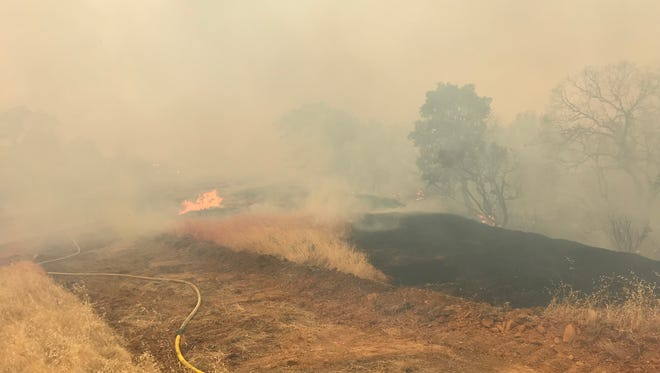 A fire off Quartz Hill Road Sunday afternoon threatened to jump the road in north Redding.