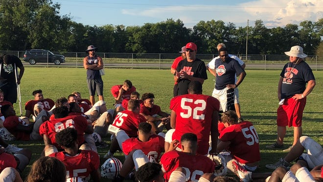 Oakland coach Kevin Creasy talks to players following Tuesday's practice. The Patriots, who are preparing for visiting RePublic Friday, are recovering from a tragedy over the weekend in which a former player was shot and killed and a current player was also shot.