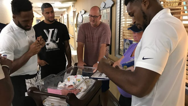 Titans safety Kevin Byard signs an autograph while cornerback Logan Ryan and safety Kenny Vaccaro chat with Clint and Candice Pewitt about their newborn daughter, Cailey Marie, during a visit Tuesday to Saint Thomas Midtown Hospital.