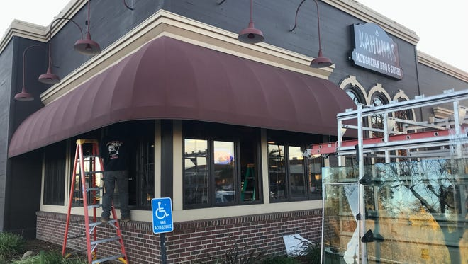 Workers replace windows that were broken Sunday night after a group of people attacked the Churn Creek Road restaurant. Police said three juveniles have been arrested.