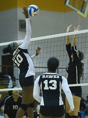 Harrison sophomore middle Kristen Hankins makes a kill Thursday as teammate Olivia Perkins looks on.