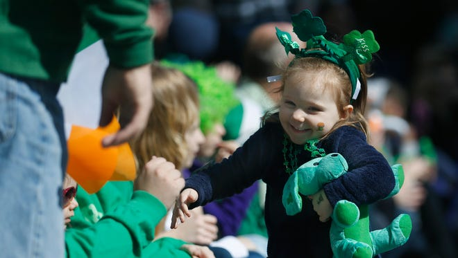 Jacqueline Larkin, 2, of East Rochester dances around on Main Street in Rochester during the St. Patrick's Day Parade.
