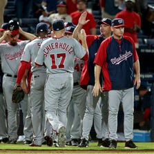 Sep 15, 2014; Atlanta, GA, USA; Washington Nationals manager Matt Williams (9) celebrates with right fielder Nate Schierholtz (17) and others after their win over the Atlanta Braves at Turner Field. The Nationals won 4-2. Mandatory Credit: Jason Getz-USA TODAY Sports