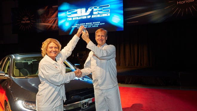 Michelle Christianson (left), Honda Manufacturing of Indiana associate in the vehicle quality department, hands President Bob Nelson the key to the redesigned 2016 Honda Civic sedan at the line-off ceremony.