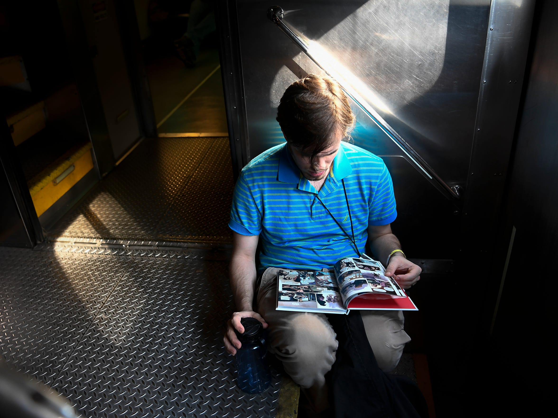 Joey Christian reads a book as he rides the Music City