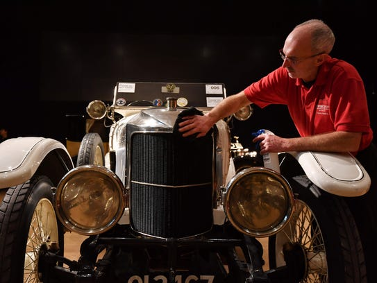 An employee prepares a 1914 Prince Henry Vauxhall for