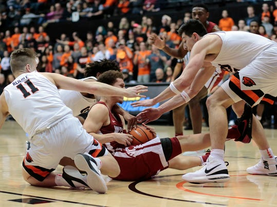 Washington State's Malachi Flynn center, tries to protect the ball from Oregon State's Zach Reichle (11) and Drew Eubanks, right, in the first half of an NCAA college basketball game in Corvallis, Ore., Thursday, Feb. 8, 2018. (AP Photo/Timothy J. Gonzalez)