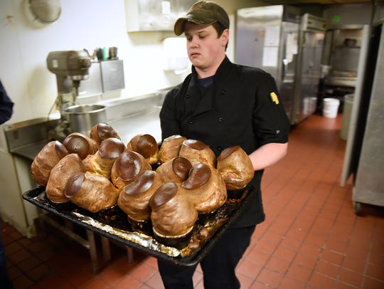 Kitchen manager Jordan Lenz takes a tray of fresh popovers