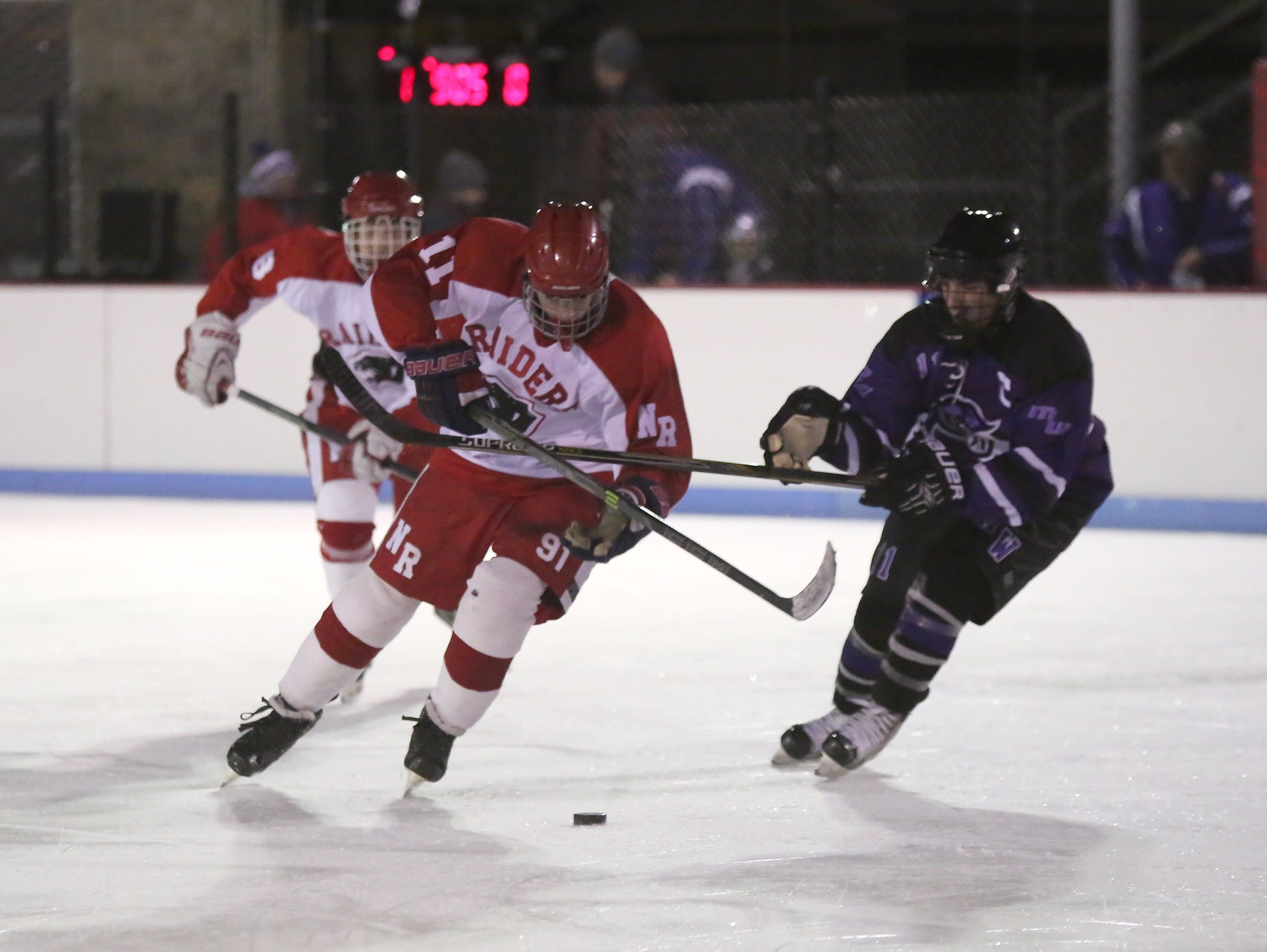 North Rockland's Chris Hilliard (11) works the puck across the blue line during the first annual Winter Classic Hockey Tournament against Monroe-Woodbury at the Bear Mountain Ice Rink in Tompkins Cove on Friday, Dec. 18, 2015.