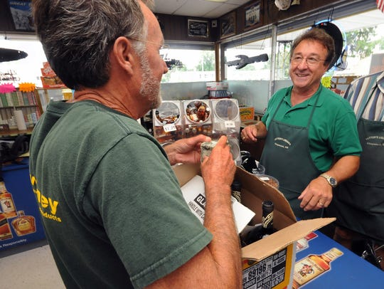 Paul DiAntonio serves a customer in his liquor store