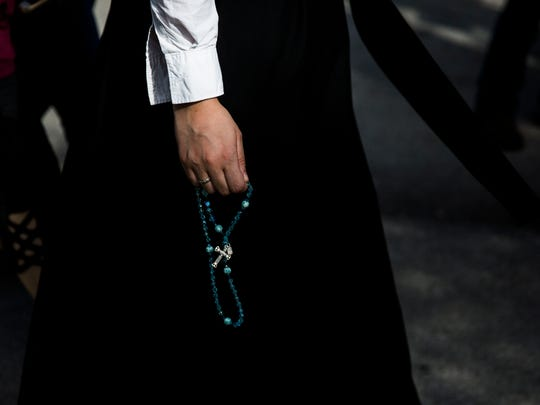 A student dressed in a habit walks to orientation holding a rosary during Marjory Stoneman Douglas High School's back-to-school orientation day in Parkland on Sunday, Feb. 25, 2018.