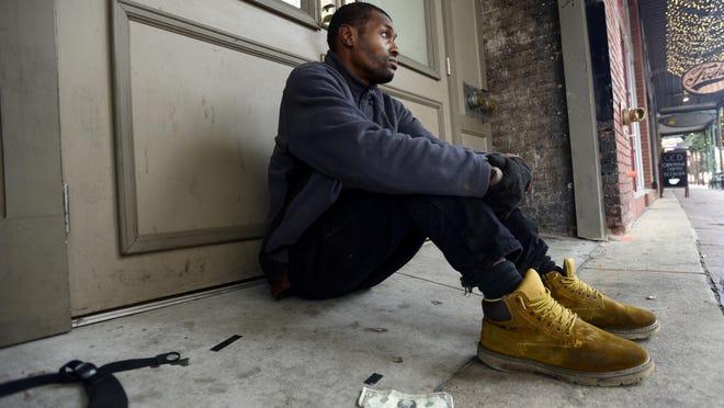 An unnamed homeless man sits along Palafox Street next to a starter dollar.