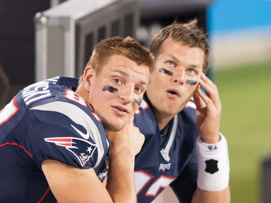 Patriots tight end Rob Gronkowski (87) and quarterback Tom Brady (12) sit on the bench during a preseason game.
