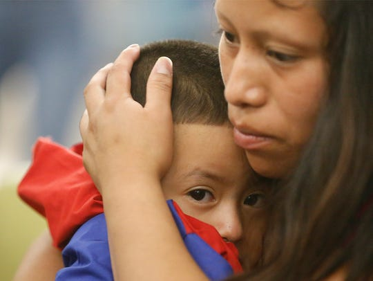 Maria holds her 4-year-old son, Franco, after he arrived