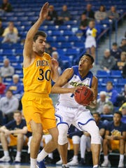 Drexel's Alihan Demir (left) defends a drive by Delaware's