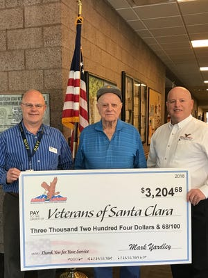 Cary Huff of Eagles Landing (right) presents more than $3,200 to the veterans of Santa Clara. Tony Moore (left) is a veterans state officer and  Chester Snow is a patron.