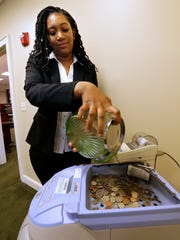 Dominique Steed, universal banker for Town Bank, 13150 Watertown Plank Road in Elm Grove, counts change in the bank's coin sorting machine.