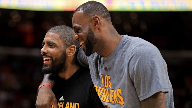 Kyrie Irving and LeBron James of the Cleveland Cavaliers laugh during a game against the Miami Heat.