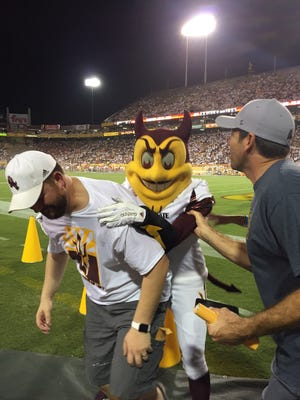Tempe Councilman David Schapira bends over in pain after Sparky jumped on his back Friday.