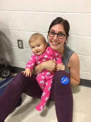 Cincinnati native Vanessa Phelan, now of Des Moines, takes part in the Iowa caucus Monday with daughter Zoe in tow.
