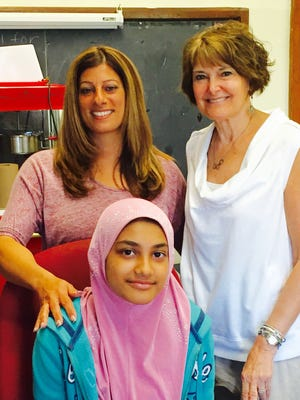 Former Bookstock essay winner Nazria Begum, center, is joined by the teacher who encouraged her two years ago, Michele Pizzo (left) and Bookstock BEST Awards coordinator Judy Robinson (right) at Davison Elementary/Middle School on May 6, 2016.