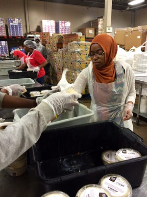 Makkiya Petross of Al IKhlas Training Academy in Detroit was one of several Muslim volunteers who helped pack food in July 2015 at Gleaners Food Bank in Detroit, for the Michigan Muslim Community Council's annual program to help the hungry during the Ramadan season.