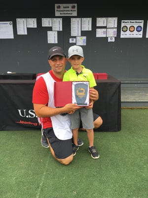 6-year-old Isaiah Adel poses with his father, Christian, after winning the U.S. Kids Golf Pennsylvania State Invitational.