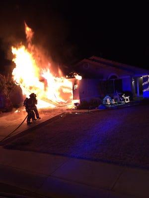Firefighters battle a garage fire in Gilbert.