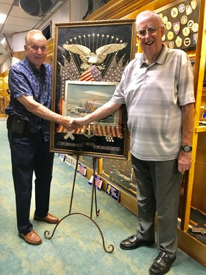 Collector H.A. Freels, right, and DeVoe Moore pose with the 1876 Japanese silk embroidery and painting that Freels recently donated to Moore's Tallahassee Auto Museum. The artwork was given to Freels' father in 1904 by the artist's family.