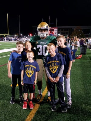 Cathedral running back Markese Stepp (30) poses with Ben Edwards, his brother, and Brody Stephens' brothers.